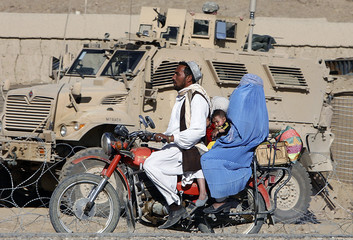 Afghan man with family rides his motorcycle at the road in the village of Ebrahihimkhel in Logar province