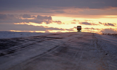 A van moves along a highway, as sunset is seen in the background, near Novosyolovo settlement some 240 km (150 miles) south of the Siberian city of Krasnoyarsk