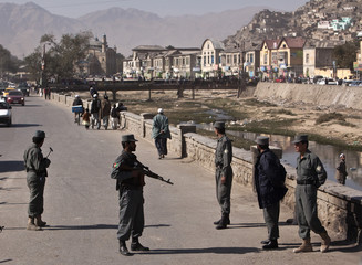 Afghan policemen keep watch at a checkpoint in downtown Kabul