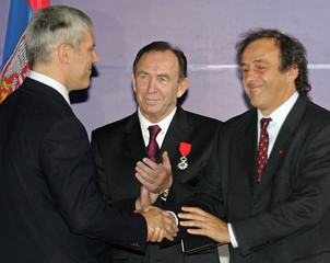 Serbian President Tadic shakes hands with French soccer icon Platini while President of Serbian FC Partizan Curkovic looks on during a ceremony in Belgrade