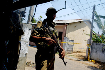 Sri Lankan policeman stands guard next to broken glass of shop after a claymore mine blast in Trincomalee