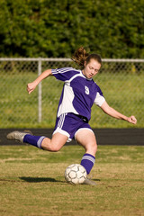 Female soccer player kicking the ball for a shot on goal