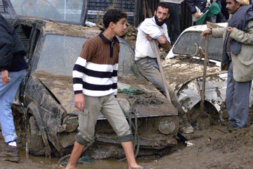 ALGERIANS DIG CARS FROM MUD AFTER HEAVY FLOODING KILLED OVER 350 INALGIERS.