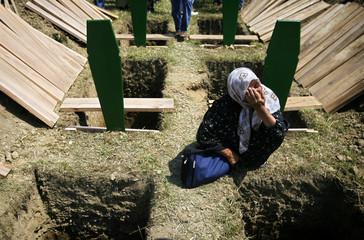 A Bosnian Muslim woman cries between graves prepared for her relatives before a mass funeral in Bratunac