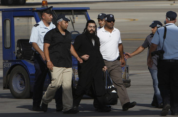Self-styled Jewish cleric Elior Noam Hen is escorted handcuffed upon arrival at Ben Gurion airport