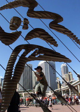 A YOUNG BOY CLIMBS UP A SCULPTURE REPRESENTING THE SYDNEY 2000 OLYMPICS LOGO.