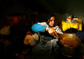 Noreen cooks for her family in her tent in Meera Tanolian refugee camp near Muzaffarabad
