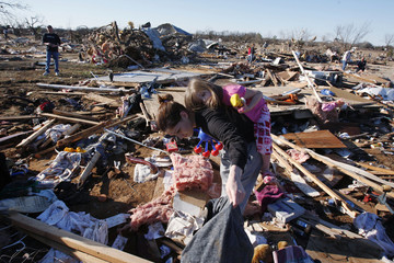 A woman carries her daughter on her back as she tries to salvage items amidst debris caused by a tornado in Lone Grove