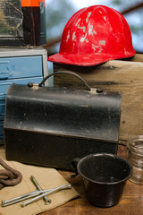 Antique coal miners lunchbox with a old, vintage aluminum hardhat in background