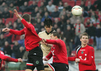FC Bayern Munich's Ballack scores despite the challenge of Hannover 96's Bergantin, Zuraw and Mertesacker during German Bundesliga soccer match in Hanover