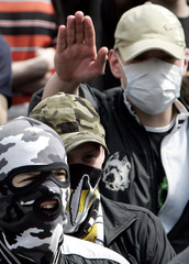A masked right-wing demonstrator gives the Nazi salute during a rally against immigration in Moscow