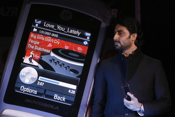 """Bollywood actor Bachchan poses with the new Motorola """"MotoRazr"""" mobile phone in New Delhi"""