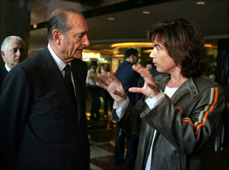 French President Jacques Chirac speaks with French musician Jean-Michel Jarre in Beijing.