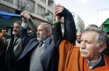 Parliament members from Hamas and Fatah hold hands during a joint protest in Hebron