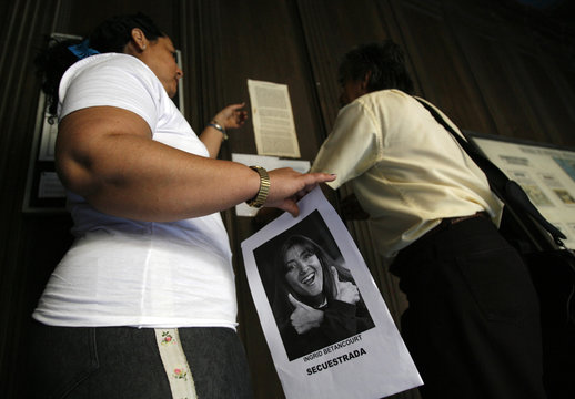 People pin up a photograph of French-Colombian hostage Ingrid Betancourt before a mass for her and fellow hostages at La Merced church in Havana