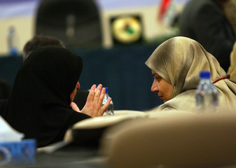 Two unidentified female members of the parliament chat prior to a session in Baghdad.
