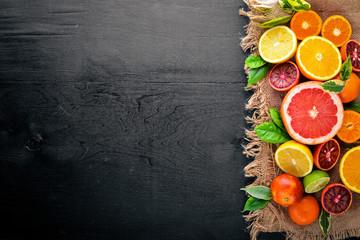 Fresh citrus fruits. Lemon orange, tangerine, lime. On a black background Wooden. Top view.