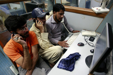 Stockbroker work during a trading session inside the trading hall at the Karachi Stock Exchange