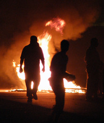 RIOTER IS SILHOUETTED BY FIRE DURING ANTI-WAR PROTEST IN BAHRAIN.