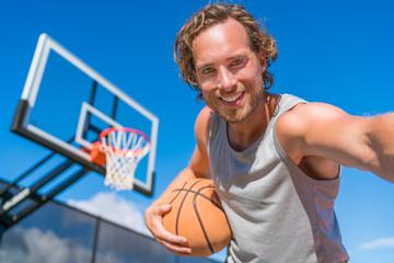 Basketball player man taking fun selfie photo at court net with basket ball.
