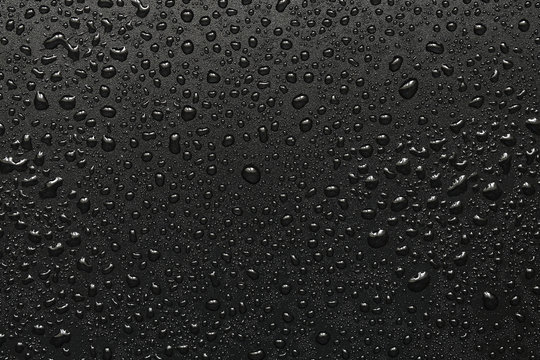 Drops of water on a black surface. The condensate. Top view. Free space.