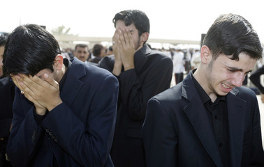 Residents react during funeral ceremony of Abdul Aziz al-Hakim at Baghdad's airport