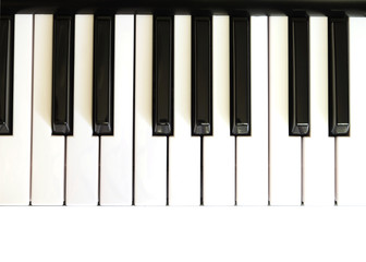 Piano keyboard with white and black keys on white background top view vertical  photo close up