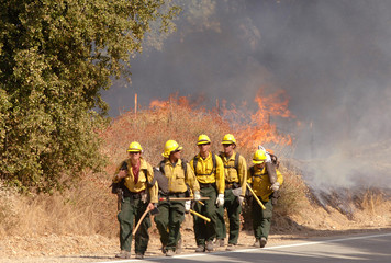 Hand crews are deployed as firefighters work to control a brushfire that threatened homes in Santa Clarita