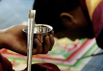 TIBETAN MONK PREPARES TO LOAD CHAK PHUR WITH COLORED SAND WHILE WORKINGON MANDALA.
