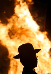 Ultra-Orthodox Jewish man is silhouetted by a bonfire during Lag Ba-Omer festivities in Jerusalem