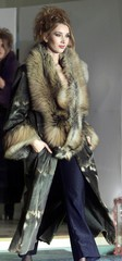 Model Alina Andrei takes the catwalk dressed in a red fox fur trimmed leather coat at a fashion show..
