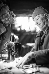 Man with sewing machine bw