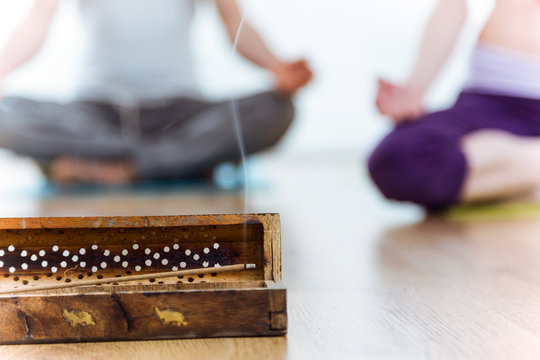 Close-up of incense stick, behind couple doing yoga.
