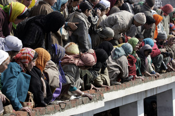 People look at the body of Mohammad Haneef during his funeral in Noor Pora