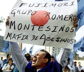 """A PROTESTER HOLDS A SING THAT READS - """"FUJIMORI AND MONTESINOS KILLER'S MAFIA""""."""