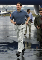AL GORE DASHES ACROSS AIRPORT TARMAC IN THE RAIN TO GREET CROWD.