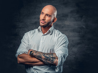 Portrait of shaved head male in a white shirt with tattooed crossed arms.