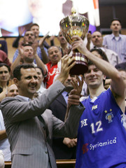 Syrian president al-Assad hands President's Cup trophy to Bashayani, Al-Jala basketball team captain, in Damascus