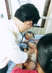 A FILIPINO DOCTOR CHECKS A BOY WHO ESCAPED ABU SAYYAF CAPTORS.