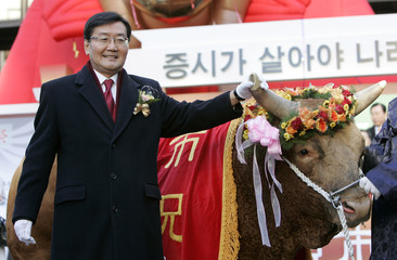 Jun, chairman of the regulatory Financial Services Commission, holds a bull's horn during the opening ceremony of the stock exchange market for the new year at the Korea Exchange in Seoul