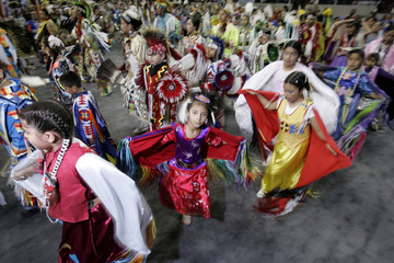 Tiny Tot dancers swirl as the Grand Entry begins the Denver March Pow Wow in Denver
