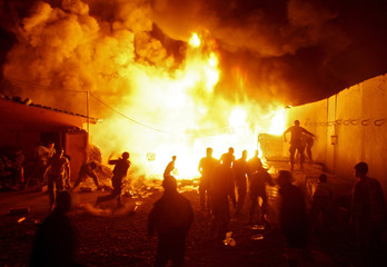 U.S. Army soldiers fight a blaze which started after a mortar round fired by insurgents ignited a fuel truck at their operating base in Baiji