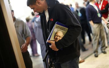 A person holds a book of billionaire financier and Berkshire Hathaway CEO Warren Buffett during the annual Berkshire Hathaway shareholders meeting in Omaha, Nebraska