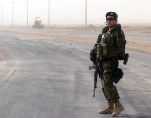 Japanese Defense Force soldier stands watch near construction project in southern Iraq town of Samawa.