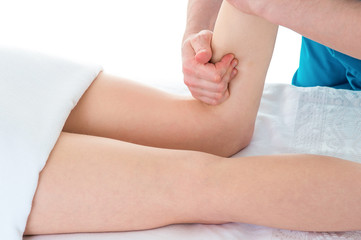Doctor is stretching woman leg on physiotherapy massage session.
