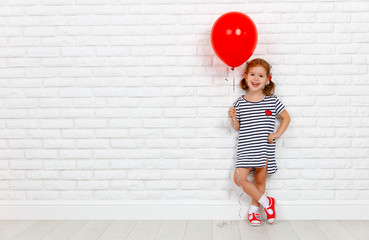 Happy funny child girl with  red ball near an brick wall.