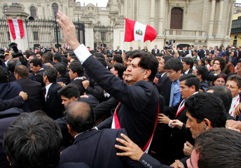 Peru's new President Garcia waves while surrounded by security guards in Lima