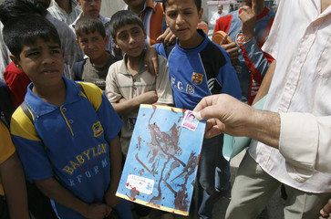 A teacher shows a bloodstained book belonging to a student killed in a mortar attack in Baghdad