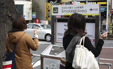Women stand at a smoking area in Harajuku