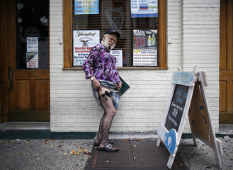 Dan Barrett shows off his stockings while taking a smoking break outside a bar dressed as a woman on Halloween in Hoboken, New Jersey